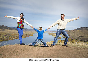 happy family holding hands together on the mountain