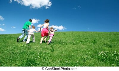 Happy family holding hands up hill