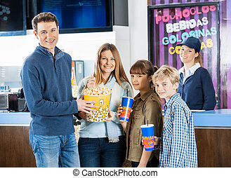 Happy Family Holding Snacks At Cinema Concession Stand