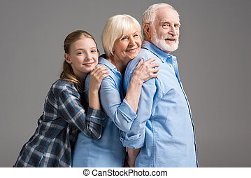happy family hugging and looking at camera isolated on grey in studio