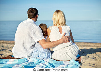 happy family hugging on summer beach