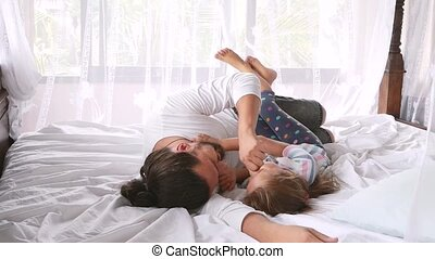 Happy Family Idyll Little Child Daughter Jump On Father Arms And They Fall On A Bed. HD