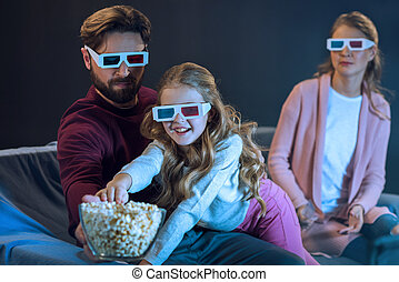 Happy family in 3d glasses watching movie and eating popcorn