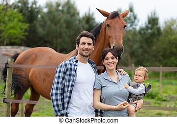happy family in a horse farm