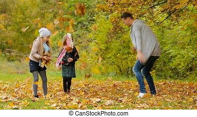 Happy family in autumn park enjoy warm day