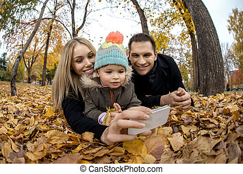 happy family in autumn park - happy family with little child...