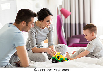 happy family in bed at home or hotel room