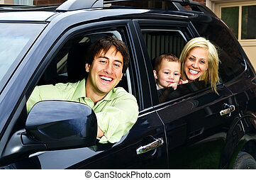 Happy family in car - Happy young family sitting in black...