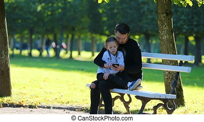Happy family in fall. Father with smartphone and little kid in fall outdoors