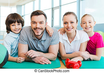 Happy family in fitness club. Happy sporty family bonding to each other while lying on exercise mat together