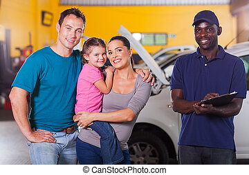 happy family in garage with auto mechanic