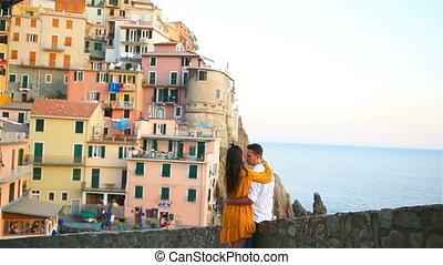 Happy family in honeymoon background old amazing village of Manarola, Cinque Terre, Liguria, Italy