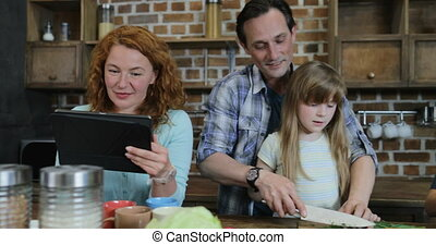 Happy Family In Kitchen Cooking, Father And Daughter Chopping Vegetables While Mother Browsing Recipe In Internet With Digital Tablet