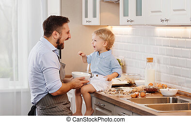 happy family in kitchen. father and child baking cookies