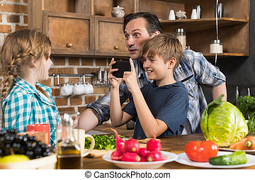 Happy Family In Kitchen, Father And Son Taking Photo Of Daughter Cooking Food On Cell Smart Phone