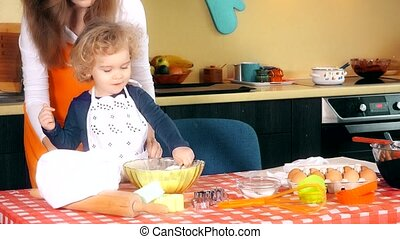 happy family in kitchen. mother and child daughter preparing dough, bake cookies