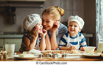 happy family in kitchen. mother and children preparing dough, bake cookies