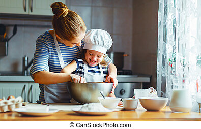 happy family in kitchen. mother and child preparing dough,...