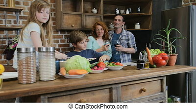 Happy Family In Kitchen, Parents Looking At Children Cooking Food Together Chopping Vegetables