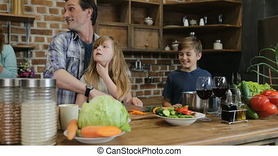 Happy Family In Kitchen Preparing Food, Mother Looking At Father And Children Cooking Together At Home