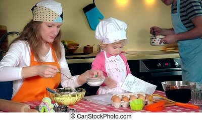 happy family in making cookies at home. Father mother and daughter together