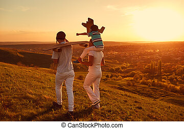 Happy family in nature at sunset.
