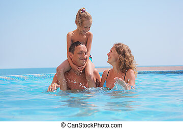happy family in pool on sea background. Daughter sits on fathers shoulders