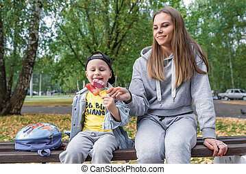 Happy family, in summer in city sitting on bench. Young woman mom, eats ice cream with son, little boy 3-5 years old, having fun and rejoicing. Break for a delicious dessert in autumn park.