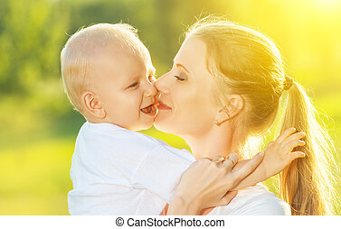 happy family in summer. mother kissing her baby