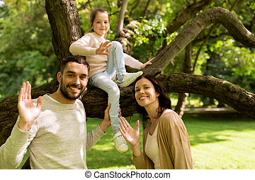 happy family in summer park waving hands