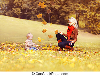 Happy family in the autumn sunny park, mother playing with her child throw yellow leaves