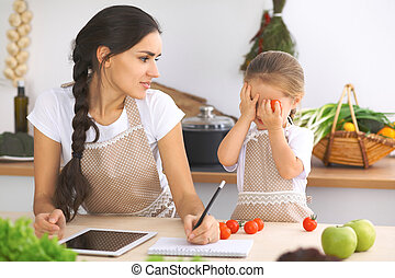 Happy family in the kitchen. Mother and child daughter make ...