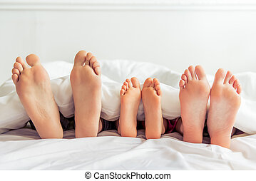 Happy family in the morning - Feet of mother, father and...