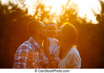 Happy family in the park evening light. The lights of a sun. Mom, dad and baby happy walk at sunset. The concept of a happy family