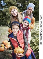 Happy family in the pumpkin field
