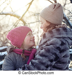 Happy Family in Winter Park. Mother and Daughter looking at each other