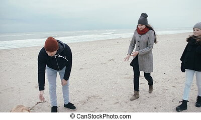 Happy family is playing with a dog on the beach.