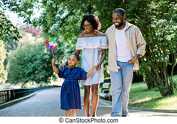 Happy family, joyful time together outdoors. Dark skinned little girl in blue dress, blowing colorful windmill toy, while walking in park alley with her young happy parents on summer day