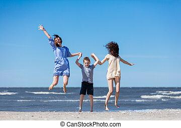 Happy family jumping high on the seashore.