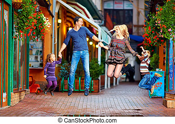 happy family jumping on colorful street