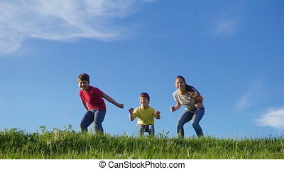 Happy family jumping on green grass hill against blue sky