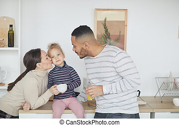 Happy Family Kissing Cute Little Girl in Kitchen
