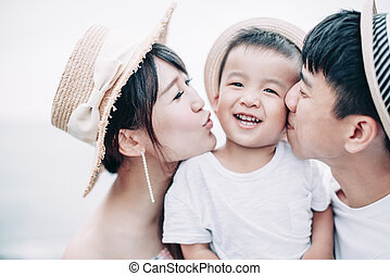 happy family kissing the child on the beach