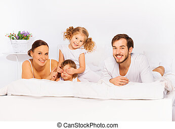 Happy family laying on white bed in white pajamas together in the morning