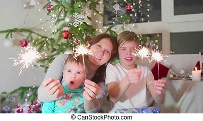 Happy family lit sparklers at the party. In the background,...