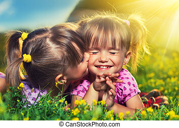 happy family. little girls twin sisters kissing and laughing...