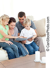 Happy family looking at a photo album sitting together in the living-room at home