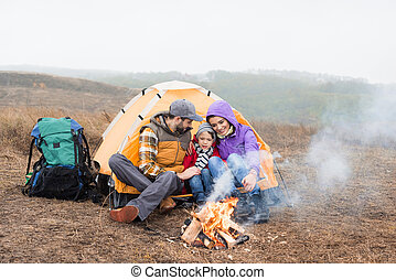 Happy family looking at burning fire