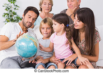 Happy family looking at globe