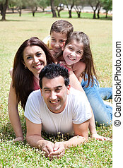 Happy family lying in the grass field